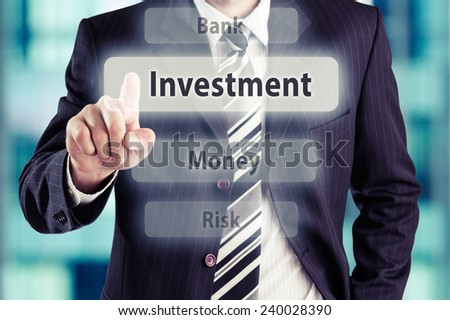 Business man pressing investment button at his office. Investment concept, toned photo. - stock photo