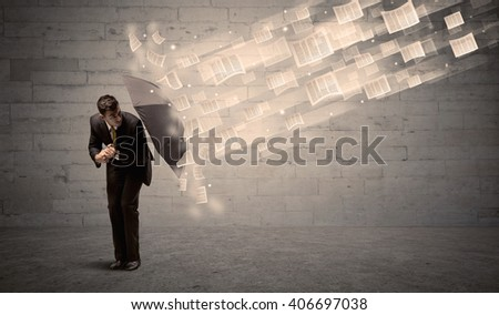 Business man protecting with umbrella against wind of papers concept - stock photo
