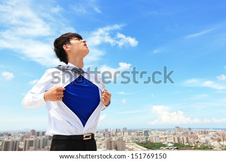 Business man pulling his t-shirt open, showing a superhero suit underneath his suit, with city background - stock photo