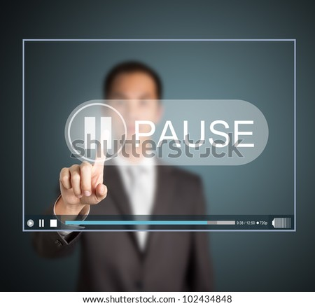 business man push pause button on touch screen to hold video clip - stock photo
