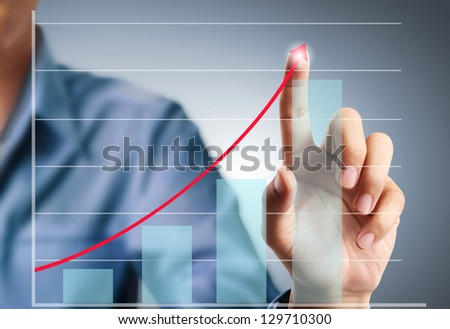 Business man pushing a graph - stock photo