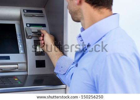 Business man put his credit card at the ATM - stock photo