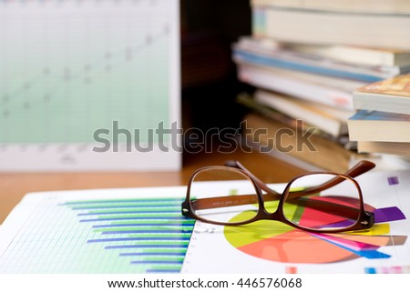 business man put his eye glasses on the book chart and graph relax time after executive meeting marketing analysis