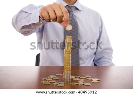 Business man putting a coin on the top of a pile - stock photo