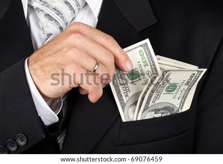 Business man putting dollar banknotes into his pocket - stock photo