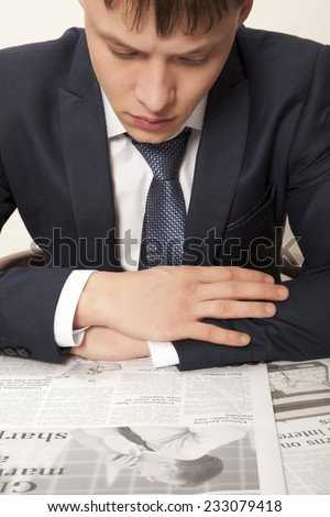 Business man reading a newspaper, gray backgrounds - stock photo