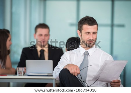 Business man reading papers in modern office - stock photo