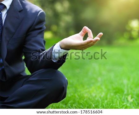Business man relaxing in a park in the lotus position. Close up - stock photo