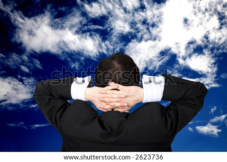 business man relaxing outdoors in front of a beautiful blue sky - stock photo