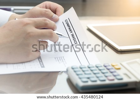 Business man review company invoice on his desk made a payment.  - stock photo