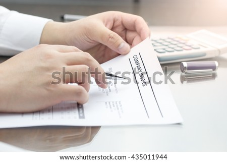 Business man review company invoice on his desk made a payment. laptop computer, pen and calculator.