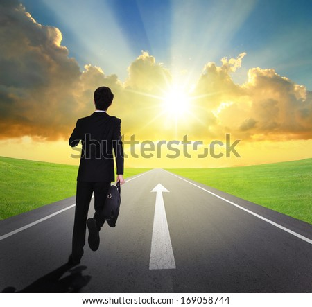 business man running forward on asphalt road with arrow , and beautiful sunset and sunshine, business concept - stock photo