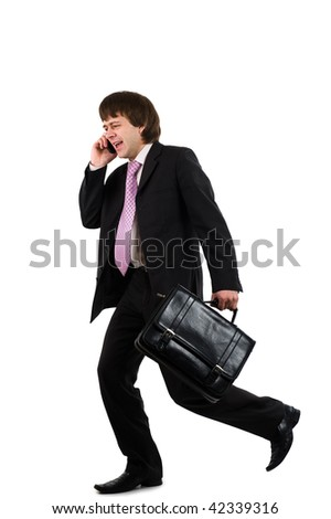 Business man running with a briefcase and speaking by phone, isolated over white background