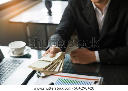 Business man sending money dollar. During negotiations on a desk with a laptop, cup of coffee and financial report.