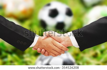 business man shake hand with football blur background - stock photo