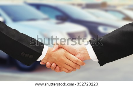 business man shake hand with rental car background - stock photo