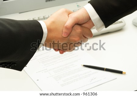 business man shake hands after signing a contract - stock photo