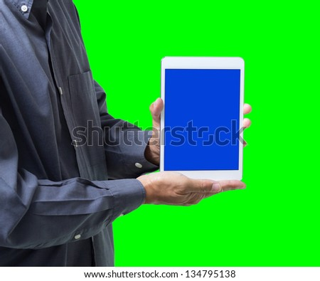 Business man show tablet with blue screen on hand, isolated on green background - stock photo