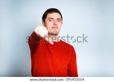 Business man showing a sign of not good, thumbs down, isolated on a gray background - stock photo