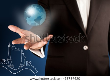 Business man showing glowing globe on the hand with world landmark in background