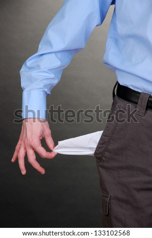 Business man showing his empty pocket, on grey background