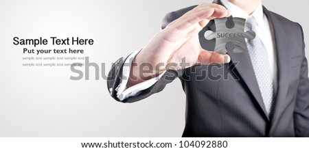 "Business man showing metal jigsaw puzzle piece with ""SUCCESS"" wording. Concept for business strength and success. - stock photo"