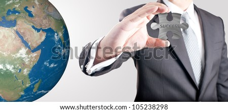 """Business man showing metal jigsaw puzzle piece with """"SUCCESS"""" wording with realistic globe in background. Concept for business strength and success. Elements of this image furnished by NASA. - stock photo"""