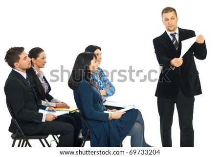 Business man showing paperwork at seminar and the team of people looking attentive to his presentation - stock photo