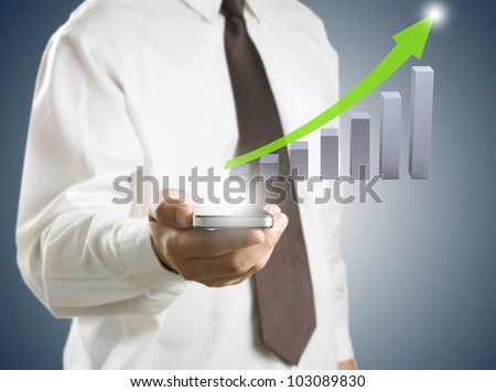 Business man showing smart phone with growth graph in background - stock photo