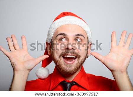 Business man showing surprise. Winter, corporate party, Christmas hat isolated portrait of a man on a gray background, studio photo.