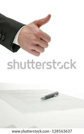 Business man showing thumbs up sign over a signed contract.  Isolated over white background.