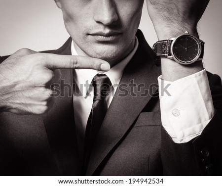 Business man showing time on his wrist watch. - stock photo