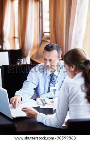 Business man shows a woman in a laptop