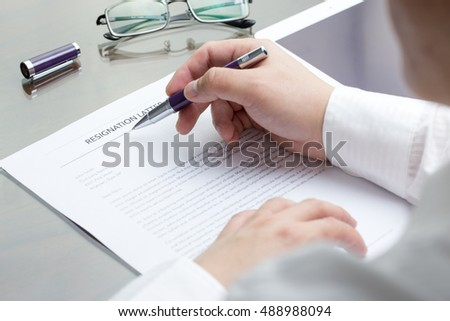 Business man signing his resignation letter on his desk before sending to his boss to quit a job. Resignation letter information with digital tablet and eye glasses