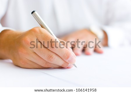 Business man signing the contract - shallow focus on signature - stock photo