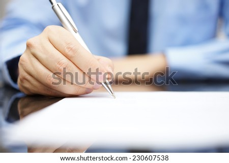 Business man signing the contract to finalize a deal - stock photo