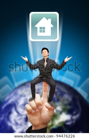 Business man sit on finger and show the house icon from the earth