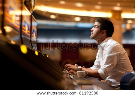 business man sitting at a slot machine, playing - stock photo