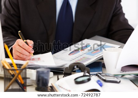 Business man sitting at office desk and working  with  documents. Close -up. - stock photo