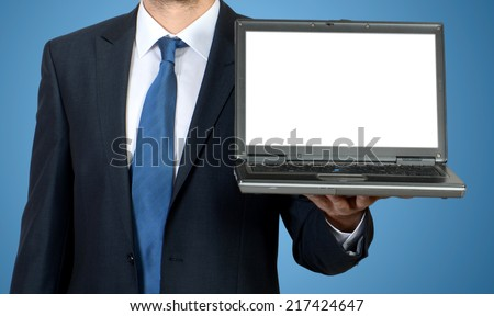 Business man sitting at office desk with laptop computer facing the camera and showing you something on laptop
