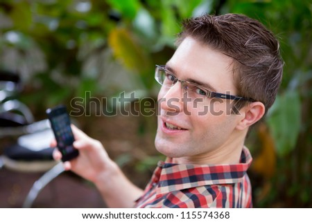 Business man sitting at table in cafe using mobile phone - stock photo
