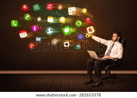 Business man sitting in office chair with laptop and colorful app icons concept on background - stock photo