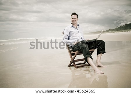 business man sitting on a chair on the beach with laptop. warm tinted image with sepia.