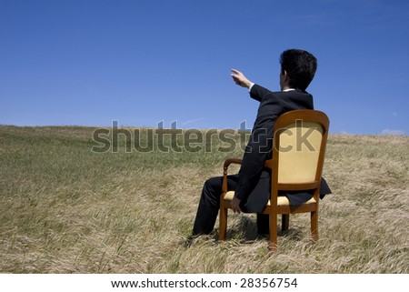 Business man sitting on a chair on the meadow pointing to the blue sky