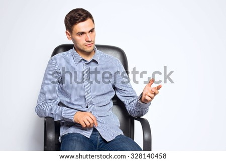 Business man sitting on chair and posing isolated on white background - stock photo