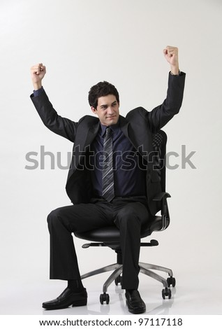 Business man sitting  on office chair with arm raised - stock photo