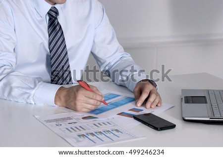 Business man sitting on the desk and working in his office.