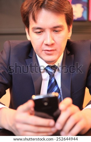 business man sitting with his phone - stock photo