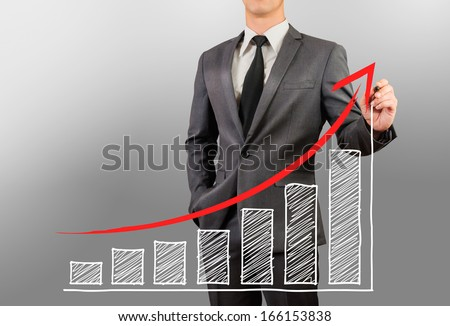 business man sketching uptrend chart and up arrow - stock photo