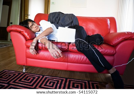 business man sleeping on the sofa with a white laptop